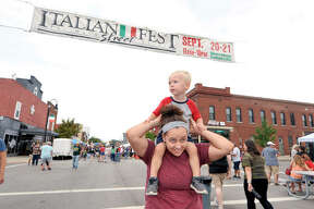 Kayla Harlin of Maryville carries her son Grayson, 2, on her shoulders as they attend the Italian festival in Collinsville Saturday. Since 1984, Collinsville has been celebrating its Italian culture and heritage.