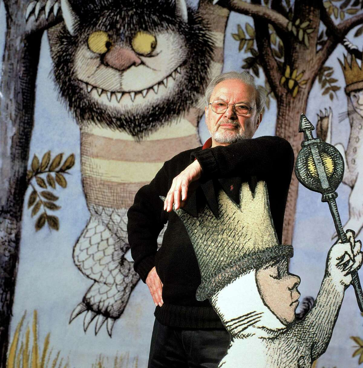 Author/illustrator Maurice Sendak standing by an life-size scene from his book