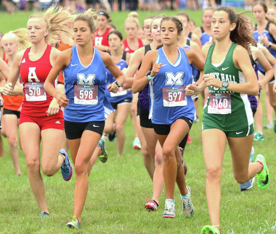 Marquette Catholic senior Riley Vickrey (bib No. 598) and freshman Kailey Vickrey (597) run together between Alton's Jessica Markel (left) and Nerinx Hall's Marisa Jacknewitz (right) at the start of the Edwardsville Invite on Saturday morning at SIUE. Photo: Greg Shashack / The Telegraph