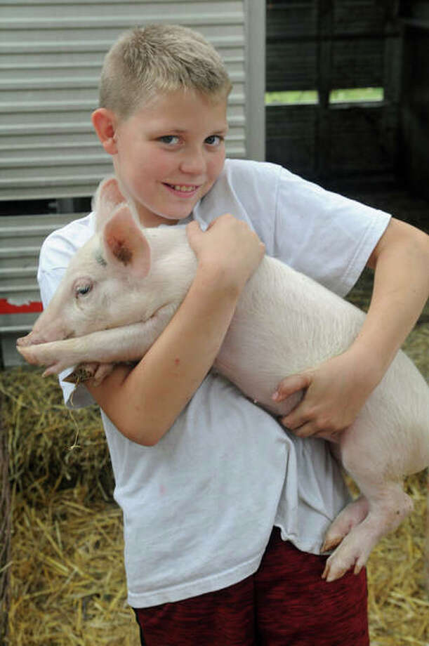 Kyle Chmieleski, 12, of McClusky handles a pig in the petting zoo at the Jerseyville Harvest Fest on Sunday.