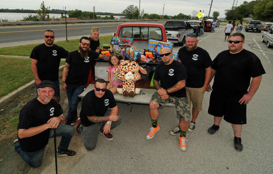 Members of the Twisted Rodz Car Club display some of the toys collected during Sunday's River Road Run for charity.