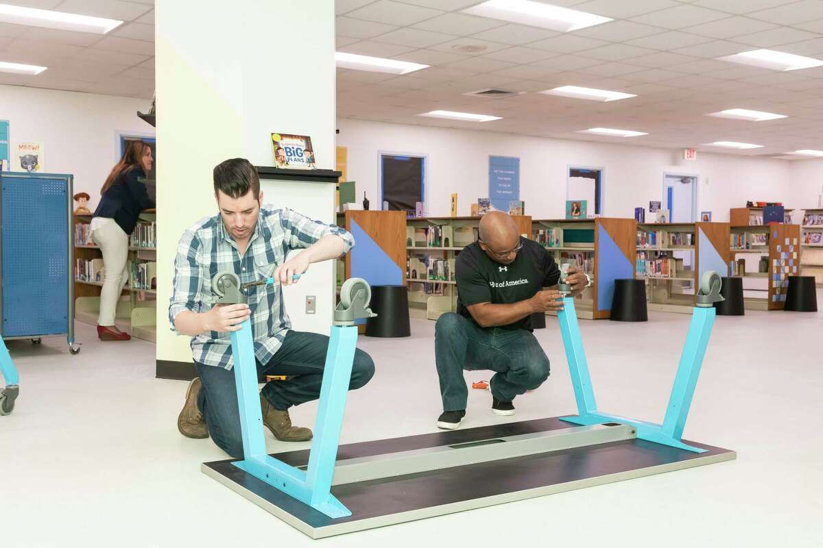 Drew and Jonathan Scott assemble furniture as part of a $100,000 makeover for the library at Burnett Elementary.