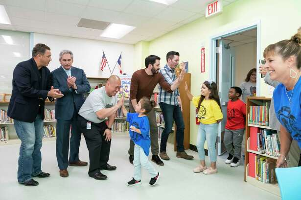 "Drew and Jonathan Scott of HGTV's ""Property Brothers"" unveil a newly renovated library for elementary students at Burnett Elementary School in Pasadena. Burnett was chosen out of thousands of nominations to receive a library makeover through the Scott brothers and the group Heart of America."