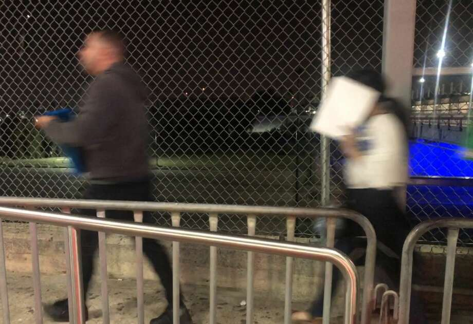 Two migrants seeking entry into the U.S. walk toward the entrance to the immigration court facility near the Gateway to the Americas Bridge. Photo: Julia Wallace/Laredo Morning Times