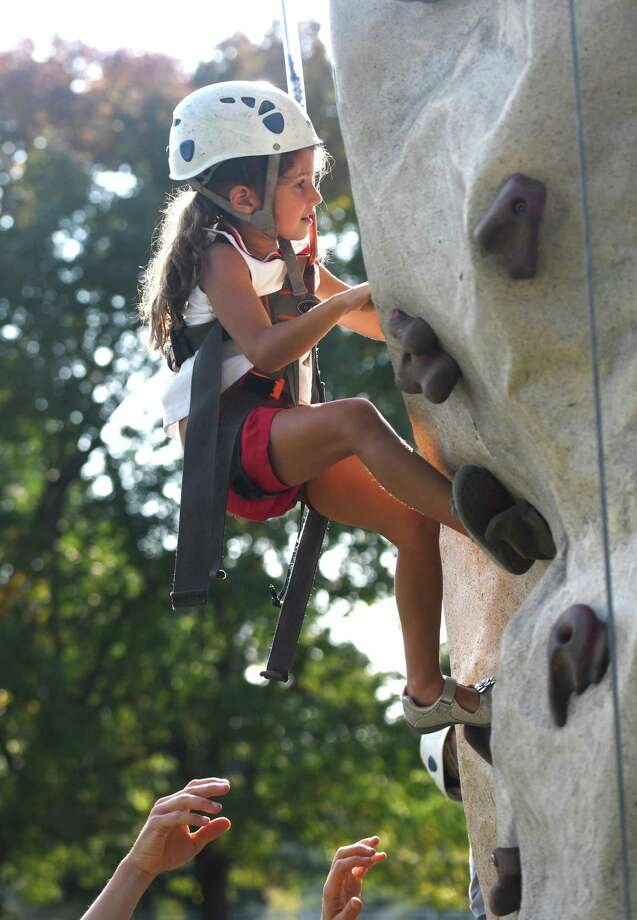 Greenwich's Cara McNally, 5, climbs the rock wall at the 20th annual Go Wild! Family Field Day at the Greenwich Polo Club in Greenwich, Conn. Sunday, Sept. 22, 2019. The event featured a variety of fun outdoor activities including hot air balloon rides, pony rides, bungee trampolines, a climbing wall, pick up soccer games, live music and more, as well as a selection of food trucks. The event supports GLT's ongoing land stewardship efforts and general operational costs. Photo: Tyler Sizemore / Hearst Connecticut Media / Greenwich Time