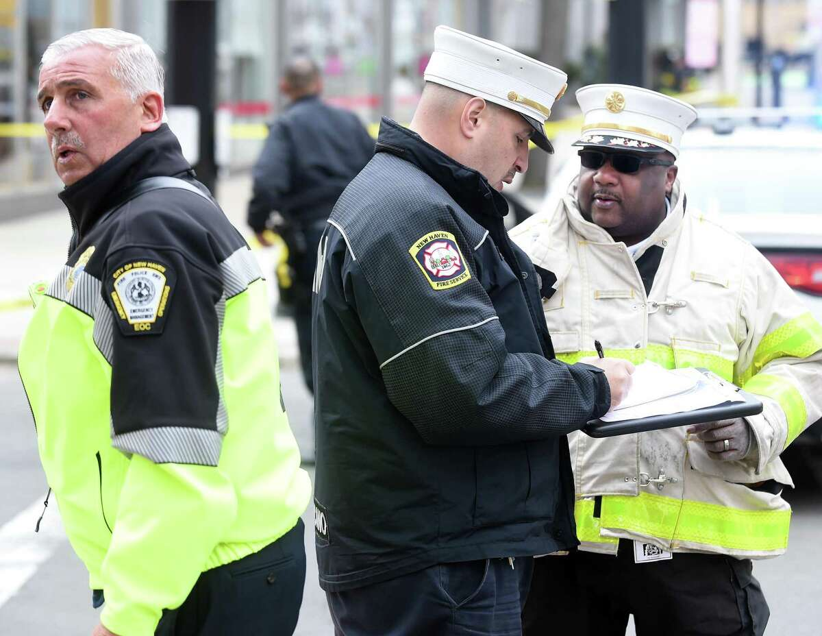 New Haven Fire Department Assistant Chief Orlando Marcano stands between Office of Emergency Management Director Rick Fontana and Fire Chief John Alston, Jr., at the scene of a reported natural gas leak on George Street in downtown New Haven on March 20, 2018.