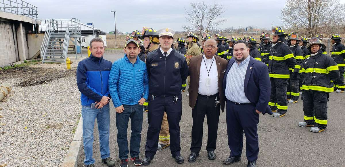 New Haven firefighters in their turnout gear outside at the New Haven Fire Department Training Facility, showing Ecuadorean firefighters and dignitaries evolutions and training. At center, Orlando Marcano.