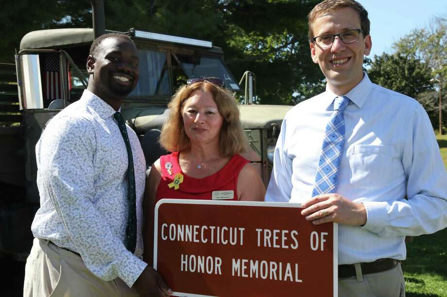 State Sen. Matt Lesser, D-Middletown, right, and state Rep. Quentin Phipps, D-Middletown, left, participated in a highway sign unveiling ceremony at Veterans Memorial Park honoring the state's veterans at the Connecticut Trees of Honor Memorial and Greater Middletown Military Museum. At center is founder and president of the Connecticut Trees of Honor, Sue Martucci. Photo: Contributed Photo