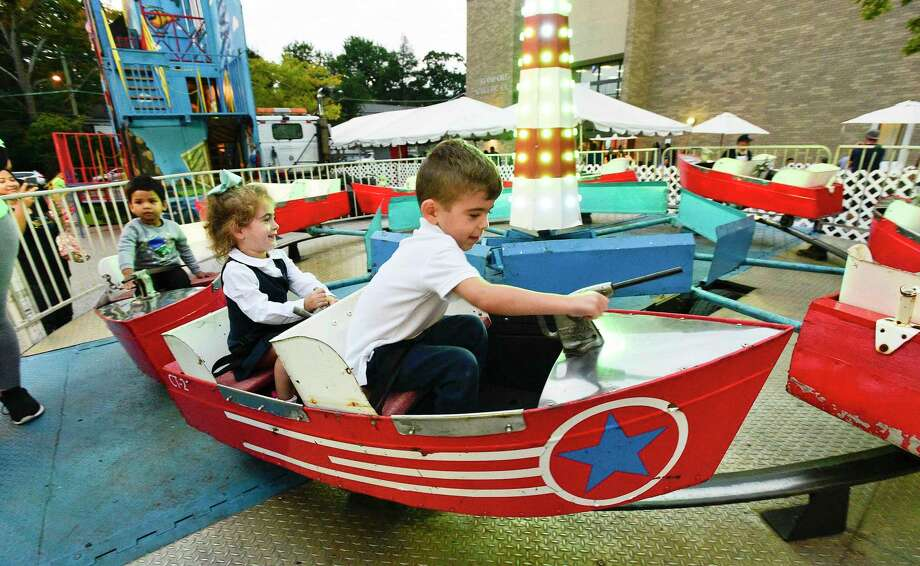 The Church of the Archangels' annual Greek Festival takes place September 26-29. Zoe Clarizio, 3, and her brother J.J., 5, both of Stamford, enjoy one of many carnival rides during last year's festival. Photo: Matthew Brown / Hearst Connecticut Media File Photo / Stamford Advocate