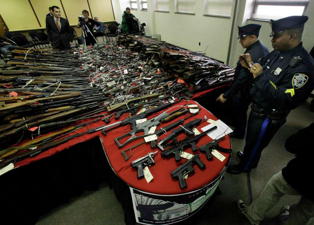 Police officers in Camden, N.J., examine guns displayed following a buyback event in 2012. A reader says only obsolete firearms are turned in during such programs.