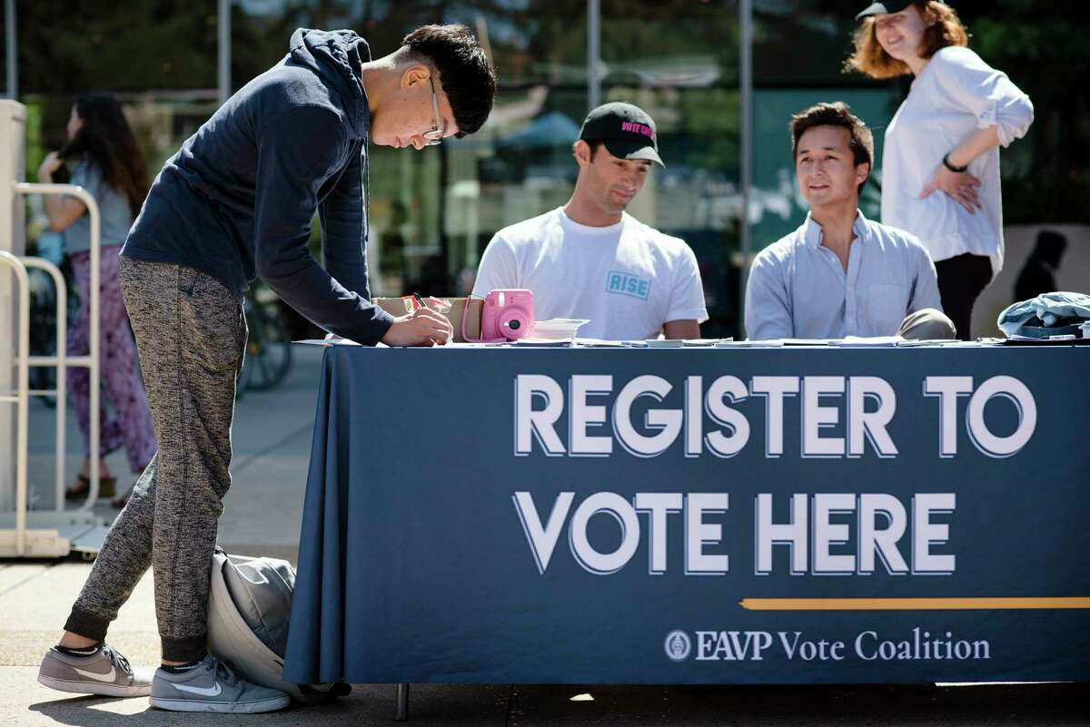 Cal student Harry Lee, left, registers to vote at the VoteCrew table during National Voter Registration Day on the UC Berkeley campus in Berkeley, Calif., on Sept. 25, 2018. This National Voter Registration Day, go out and urge others to register if they haven't yet - everyone's voice must be heard.