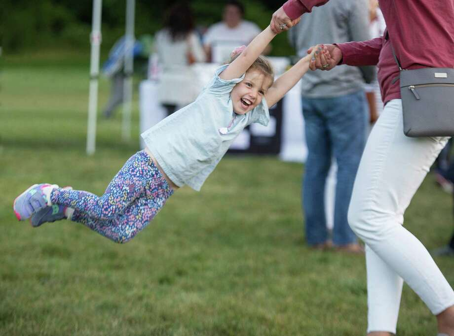 Avery Noonan, 3, of Ridgefield swings with her mom at RidgeFest, a launch party for the e-commerce website RidgefieldMarketplace.com, on Friday, Sept. 13. Photo: Bryan Haeffele / Hearst Connecticut Media / Wilton Bulletin