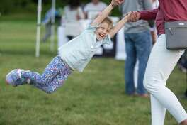 Avery Noonan, 3, of Ridgefield swings with her mom at RidgeFest, a launch party for the e-commerce website RidgefieldMarketplace.com, on Friday, Sept. 13.