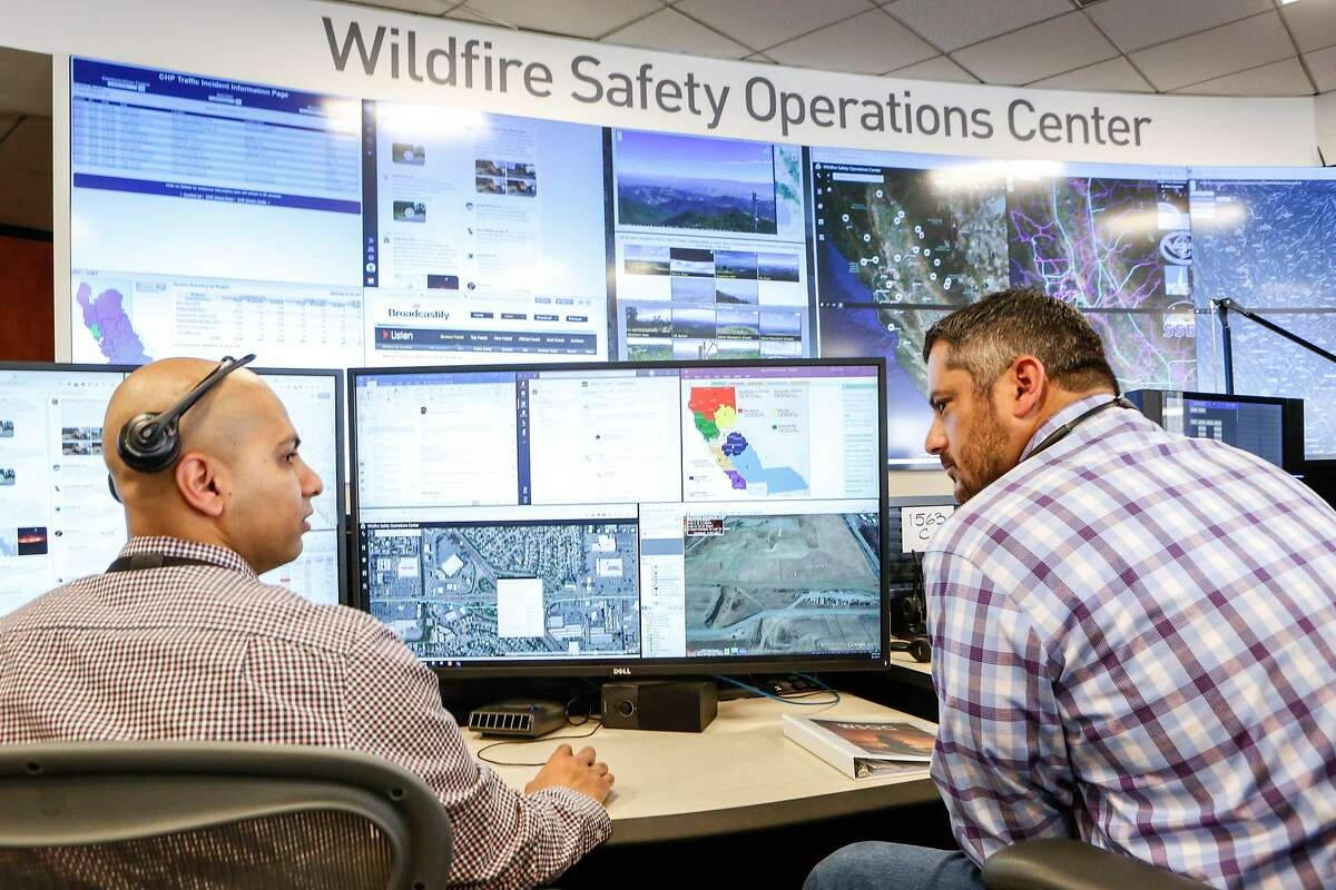 Neal Narayan and Anthony Malnati, Sr. wildfire safety operation center analysts, monitor a small fire on the 16 screen video wall and as well their stations as the media receives a tour of the hub PG&E set up in its San Francisco headquarters last year to monitor for wildfires on Monday, August 5, 2019 in San Francisco, Calif.