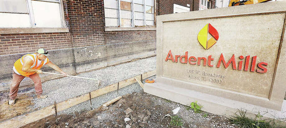 Damage from the second worst flood in recorded history goes beyond the interior of Ardent Mills. Here an employee of Stutz Excavating spreads rock for the pour of a new concrete sidewalk in front of the building on West Broadway. Floodwaters undermined the old sidewalk, causing it to crack.