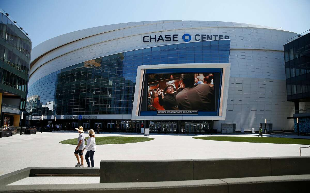 People walk across the plaza near a giant video screen at Chase Center \on Thursday, September 12, 2019 in San Francisco, CA.