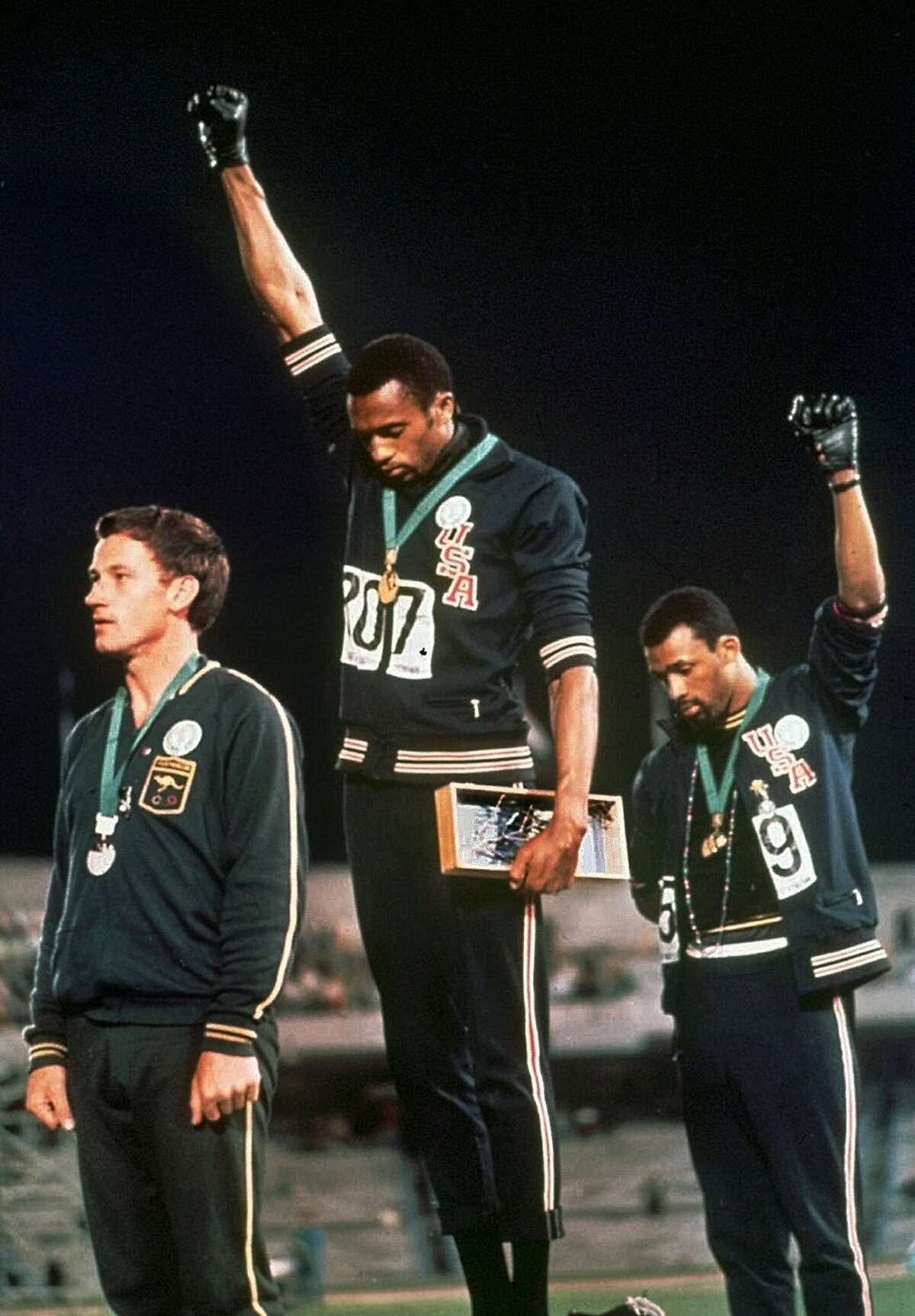 FILE - In this Oct. 16, 1968, file photo, U.S. athletes Tommie Smith, center, and John Carlos stare downward and extend gloved hands skyward in a Black power salute after Smith received the gold and Carlos the bronze for the 200 meter run at the Summer Olympic Games in Mexico City. Australian silver medalist Peter Norman is at left. Tommie Smith and John Carlos are part of the 2019 U.S. Olympic and Paralympic Hall of Fame class that will be inducted later this year.(AP Photo, File)
