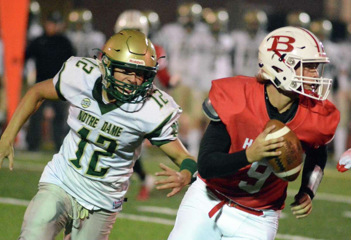 Branford quarterback Sean Kelly scrambles as Notre Dame-West Haven's Dominick Avallone gives chase during their game on Friday.