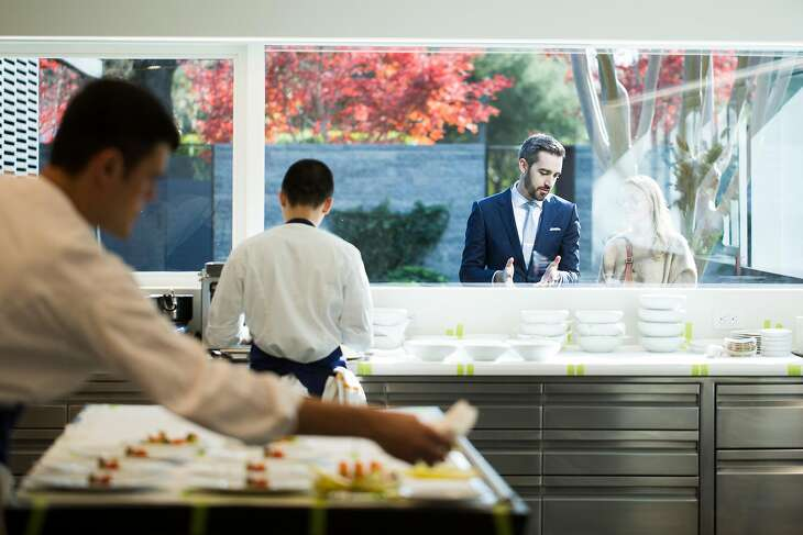 Maitre d� Nick Fitch describes the kitchen operations to a patron through the glass at the newly remodeled and expanded French Laundry in Yountville, Calif. on Saturday, Dec. 9, 2017.
