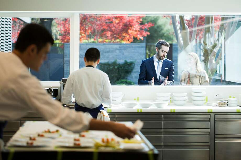 Maitre d� Nick Fitch describes the kitchen operations to a patron through the glass at the newly remodeled and expanded French Laundry in Yountville, Calif. on Saturday, Dec. 9, 2017. Photo: Stephen Lam / Special To The Chronicle