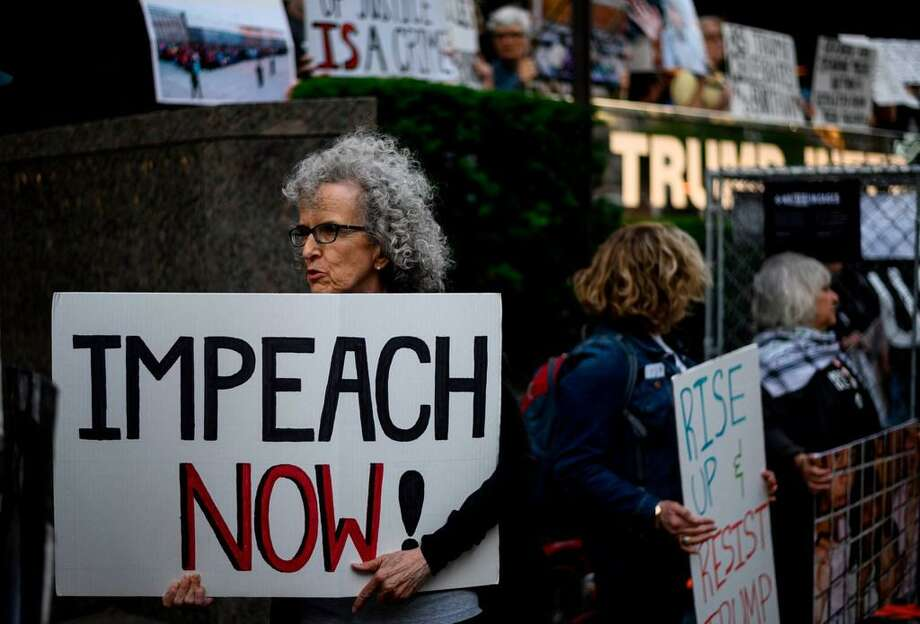 "A demonstrator with a sign reading ""Impeach now"" takes part in Trumps Birthday Protest in front of the Trump International Tower, June 14, 2019 in New York City. - A group of activists protested against his immigration policy. Photo: JOHANNES EISELE/AFP/Getty Images"