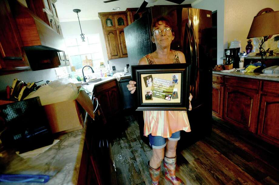 """Sheila Hight shows a photo of her husband, which she'd placed up high to keep from potential damage as she begins clean-up from several inches of flooding inside her River Bend Road home in Bevil Oaks, whose evacuation order was lifted late Sunday. Many residents were already in the process of clearing out and gutting their homes Monday morning. Hight's home got over six feet of flooding in Harvey, but she and husband Ernie were able to repair. """"You should have seen my house. It was beautiful,"""" she said. Hight lost her husband in January to cancer, """"and now I'm doing this again. So it's rough."""" Photo taken Monday, September 23, 2019 Kim Brent/The Enterprise Photo: Kim Brent / The Enterprise / BEN"""