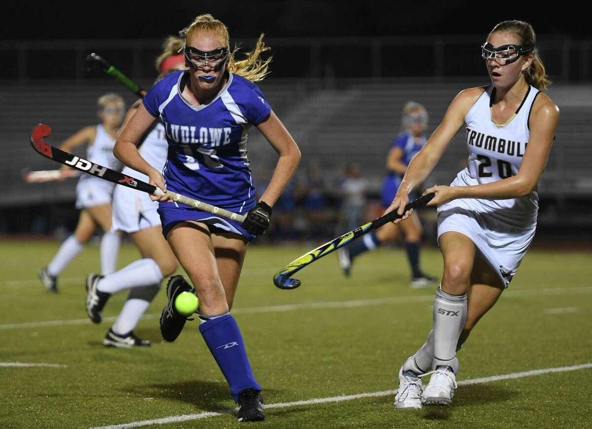 Fairfield Ludlowe's McKalynn Jacobsen, left, goes after the ball in front of Trumbull's Ella Consla in the first half of their FCIAC field hockey game on Monday in Trumbull. Ludlowe won 2-1.