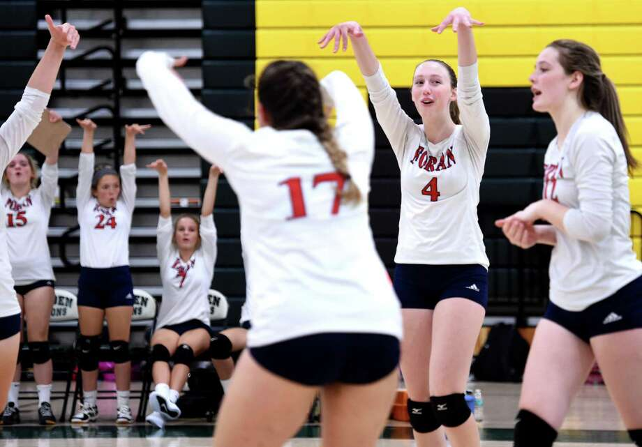 Foran's Paige Carlson, second from right, celebrates with teammates after winning a point in the second game against Hamden on Monday. Photo: Arnold Gold / Hearst Connecticut Media / New Haven Register