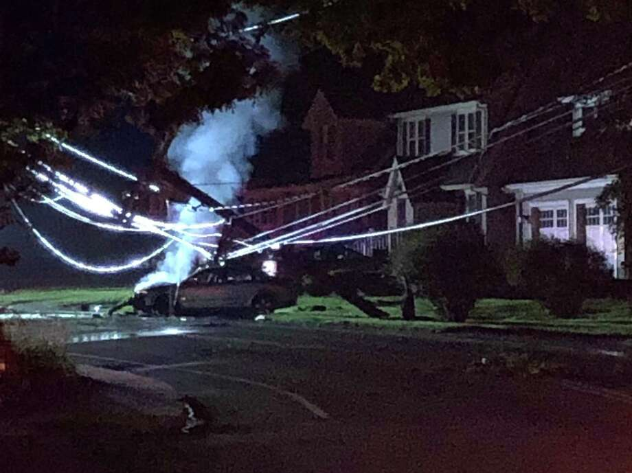 A car hit a police in a Darien neighborhood on Saturday night, causing it to be engulfed in flames. Police charged the operator, who left the car before they arrived, with operating under the influence. Photo: Kristen Riolo