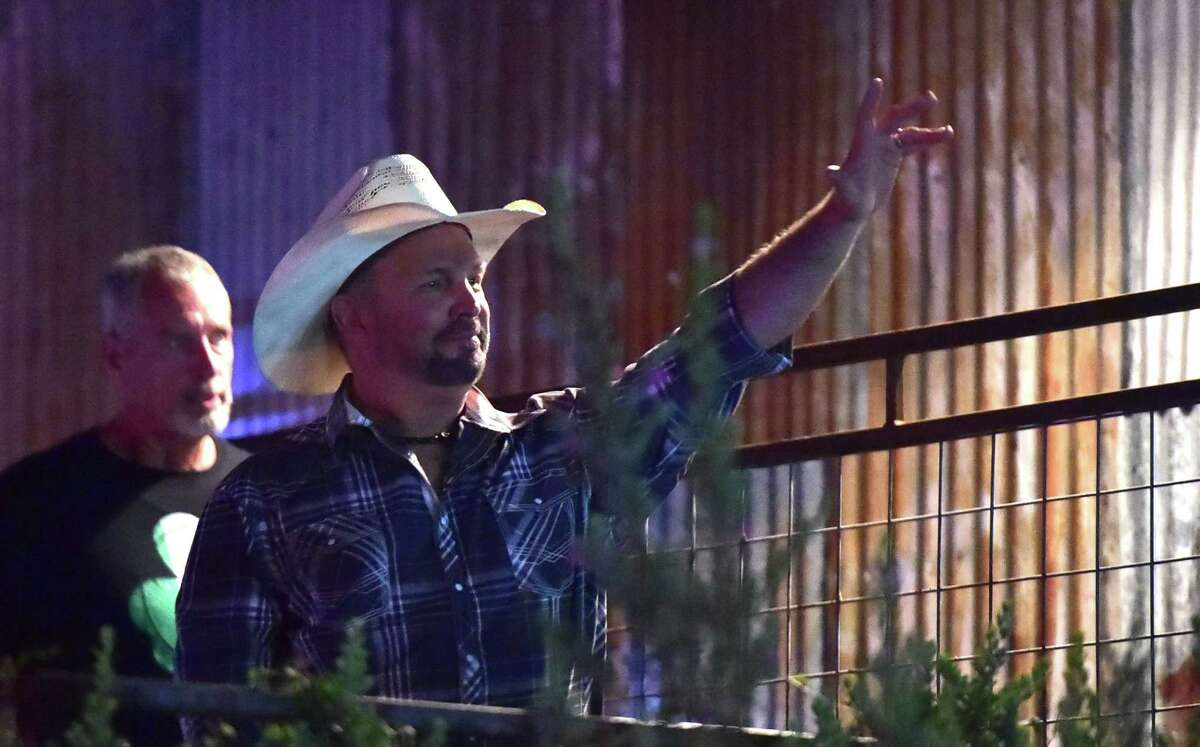 Garth Brooks waves to fans as he heads over to Gruene Hall on Monday evening as part of his