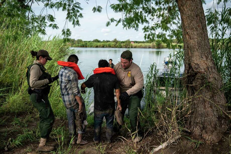 Members of a U.S. Border Patrol river unit catch and detain migrants in a field as they patrol the Rio Grande on Sept. 5 near Mission, Texas. Photo: Washington Post Photo By Jabin Botsford / The Washington Post