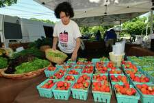 The Wilton Farmers Market is set to open on June 3, with safety measures in place to prevent the spread of the coronavirus. This photo from last year shows Ambler Farm volunteer Kathy Olstein preparing fresh produce for the market.