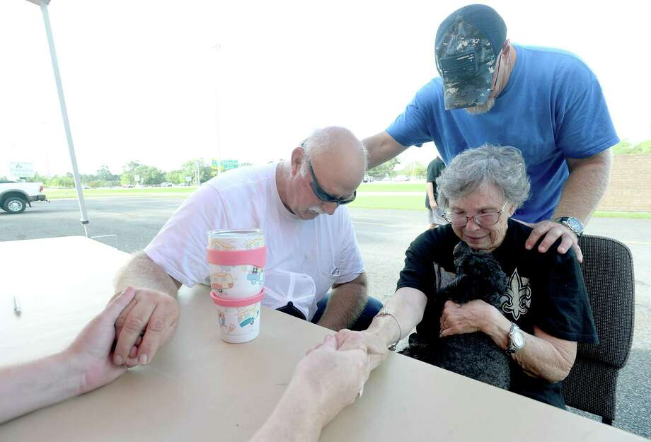 Church member and volunteer Scott Rast joins in a prayer with Rebecca and Gary Sonier and Operation Blessing's Alan Motes after they sign up for assistance at Cathedral in the Pines Church in Beaumont Monday. The Mauriceville couple had four feet of flooding during Harvey and got eight inches from Imelda. Invetween the two storms, Sonier says she's had a stroke and was overwhelmed at the thought of repairing again from flood damage. The couple were able to get their trailer out in time this go around. They lost their first trailer to Harvey. Operation Blessing has additional staff and resources on the way to the area, and within the first two hours of opening for applications had already seen almost 90 area residents sign up for assistance with cleaning and gutting their homes. Photo taken Monday, September 23, 2019 Kim Brent/The Enterprise Photo: Kim Brent / The Enterprise / BEN