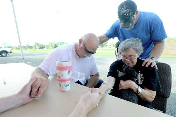 Church member and volunteer Scott Rast joins in a prayer with Rebecca and Gary Sonier and Operation Blessing's Alan Motes after they sign up for assistance at Cathedral in the Pines Church in Beaumont Monday. The Mauriceville couple had four feet of flooding during Harvey and got eight inches from Imelda. Invetween the two storms, Sonier says she's had a stroke and was overwhelmed at the thought of repairing again from flood damage. The couple were able to get their trailer out in time this go around. They lost their first trailer to Harvey. Operation Blessing has additional staff and resources on the way to the area, and within the first two hours of opening for applications had already seen almost 90 area residents sign up for assistance with cleaning and gutting their homes. Photo taken Monday, September 23, 2019 Kim Brent/The Enterprise