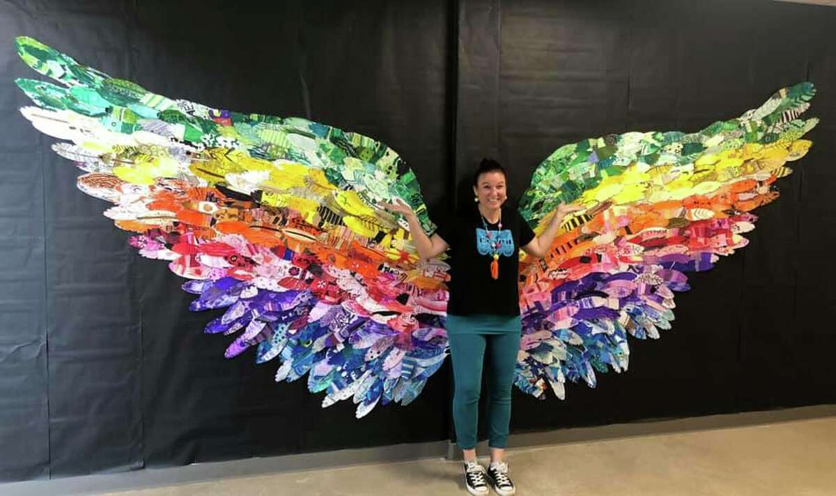 Fabra Elementary School art teacher Melissa Lecomte stands in front a winged mural created by the schools nearly 500 students.
