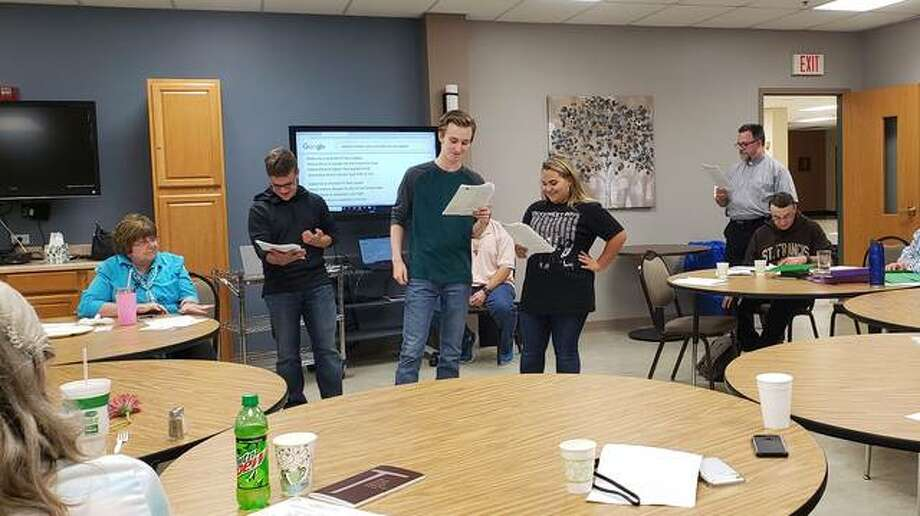 Students Patrick Boulanger (Brother Leo), Barrett Larkin (St. Francis), and Chloe Albrecht (St. Clare) presenting to Secular Franciscans (Kathy Adams in foreground, Marian Crosby, Larry Ashlock, Deacon Neil Suermann, Joseph Gassiraro) Photo: Courtesy Of McGivney Drama Club