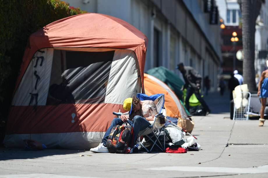 A homeless man sleeps in front of his tent along Van Ness Avenue in downtown San Francisco in this 2016 file photo. Photo: JOSH EDELSON/AFP/Getty Images