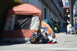 A homeless man sleeps in front of his tent along Van Ness Avenue in downtown San Francisco in this 2016 file photo.