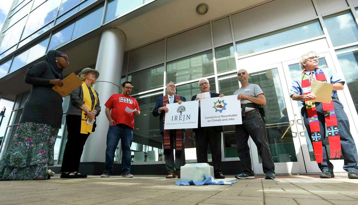 With an burial urn containing ashes from Stamford-based Castleton Commodities International's coal-fired power plant in Bow, N.H., activists call for the plant's shutdown, during a gathering in front of Castleton Commodities offices in Stamford, Conn., on Sept. 24, 2019.