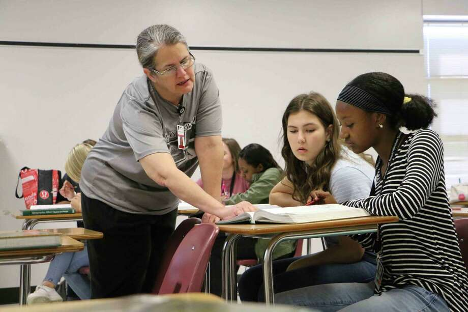 "Pearland High School teacher Patricia Ney works with students Mariah Burlew, left, and Jada Benefield. The district received a B rating from the Texas Education Agency, with 14 campuses, including all three high schools, getting A scores. ""We improved in 16 of our 23 schools,"" Superintendent John Kelly says. A D grade at an alternative school kept Pearland ISD from an A, which the district is appealing. Photo: Pearland ISD"