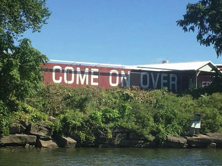 """Portland's""""Come On Over"""" sign recently got some TLC to remove overgrown foliage. Photo: Susan Bransfield /"""