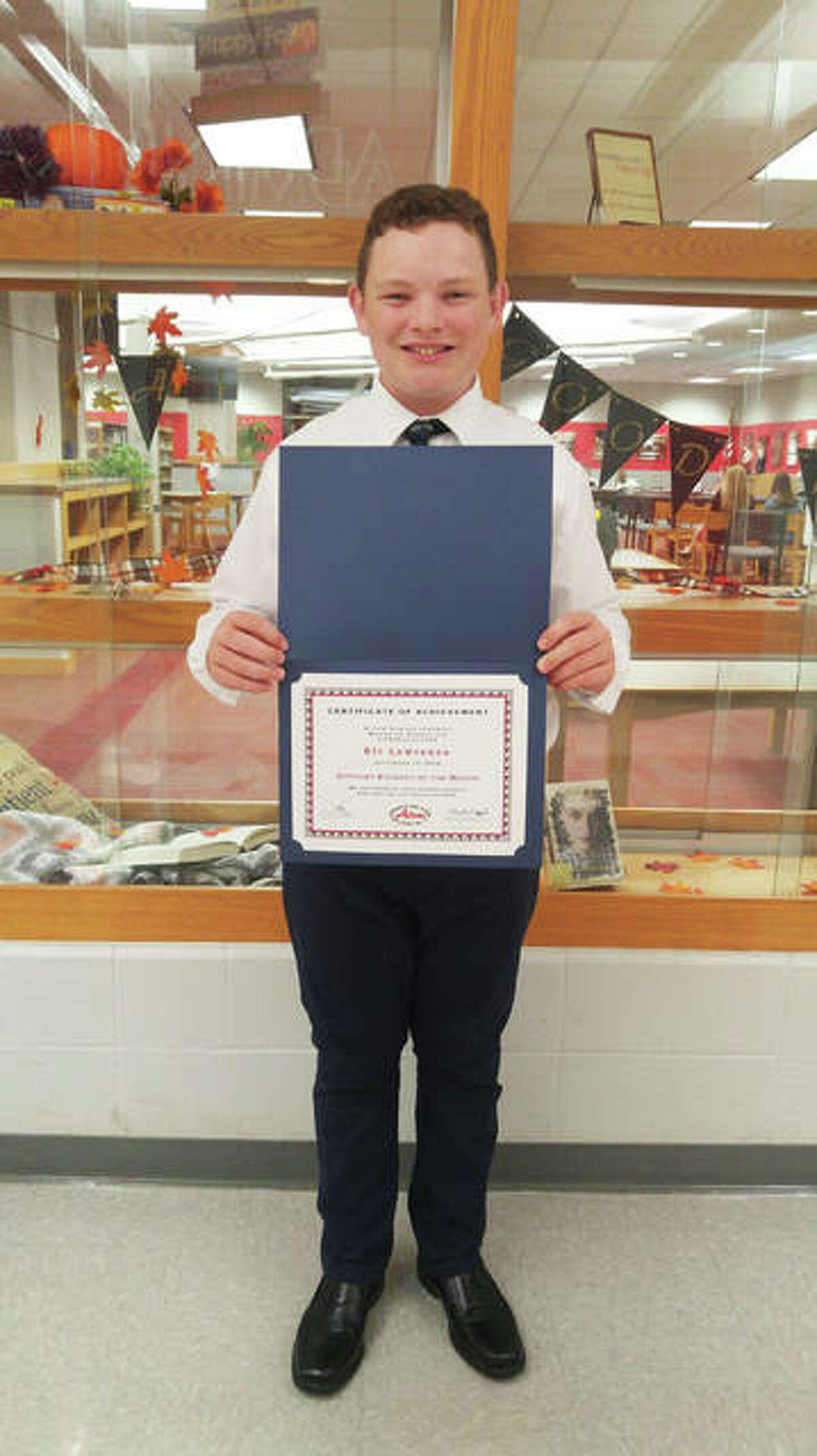 Eli Lawrence holding his award for Alton Middle School's Optimist Student of the Month for September. Lawrence received the recognition for his hard work and willingness to help others, as demonstrated in part by his willingness to learn sign language to communicate with a classmate.