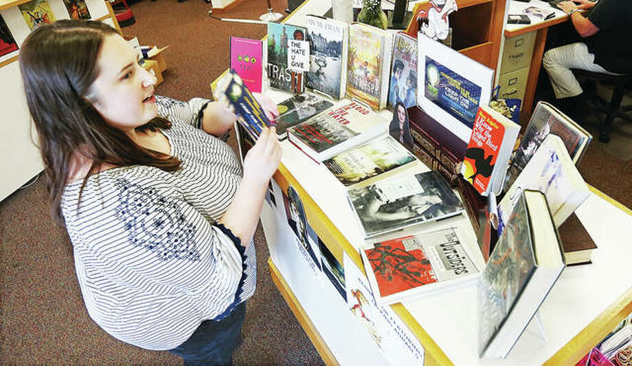 Morgan Berry, Hayner Library circulation manager, works with a display she set up for Banned Books Week in the downtown library branch on Belle Street in Alton. The annual event, Sept. 22-28, is sponsored by the American Library Association.