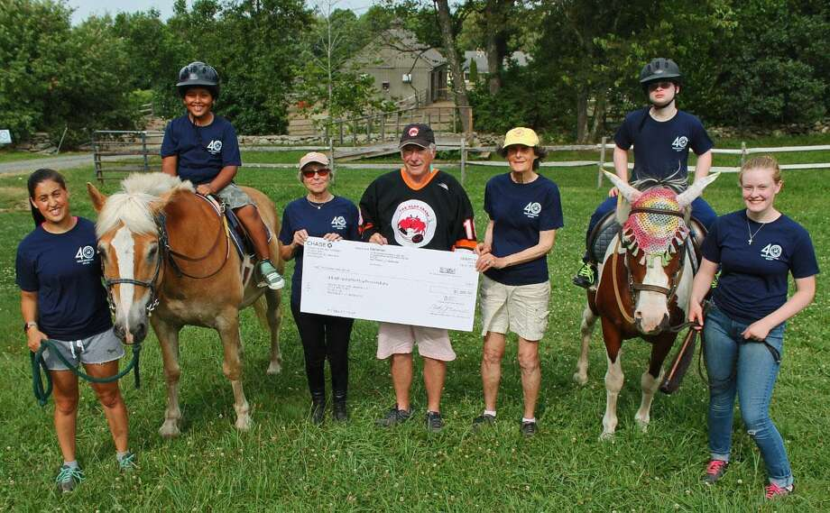 Little Britches Therapeutic Riding in Roxbury recently received $1,000 from the Old Crabs Hockey Club, providing funds for Little Britches to present an October 40th anniversary horse show. Above, Ron Faanes, center, of the Old Crabs Hockey Club Board of Directors, presents the check to Little Britches staff, volunteers and riders Samantha Sola, Liam Breunig on Chubs, Marcye Britt, Kevin Wardowski on Lucy, Emily Ciesielski and Stuart Daly. Photo: Courtesy Of Little Britches / The News-Times Contributed