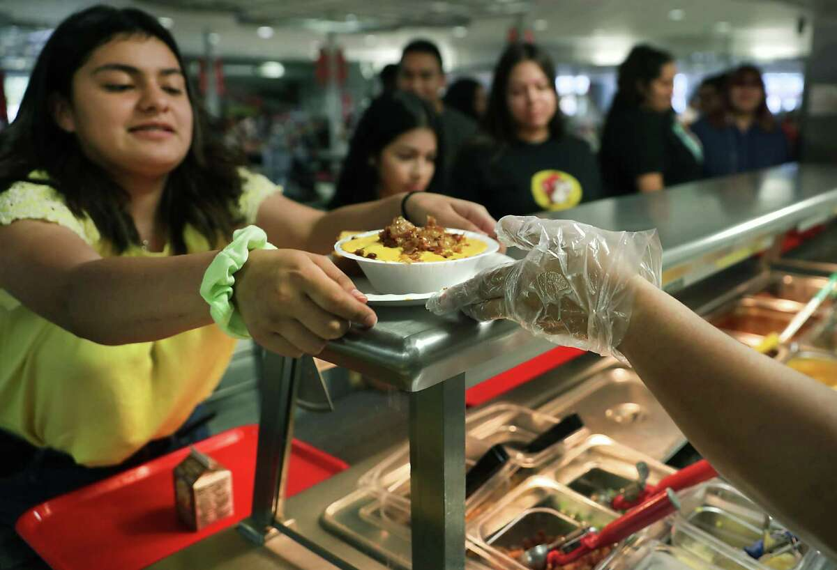 Caitlyn Escobedo, left, gets her lunch from the cafeteria line Tuesday. Students at Legacy of Educational Excellence High School buy their lunches by paying through their account or cash.
