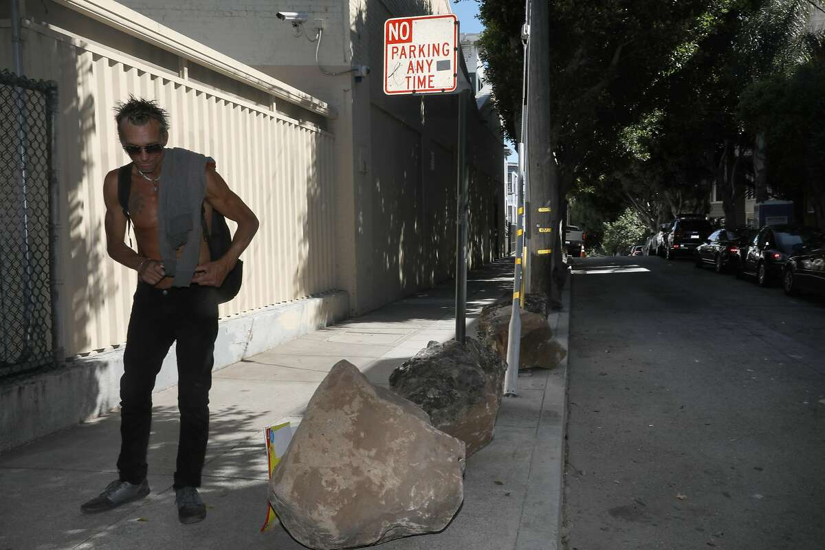 Eric Mills gets up after taking a rest on a boulder at Clinton Park just off of Dolores St. on Tuesday, September 24, 2019, in San Francisco, Calif. Someone has put boulders on the sidewalk to keep the homeless tents out and the Department of Public works has no plans to remove them.