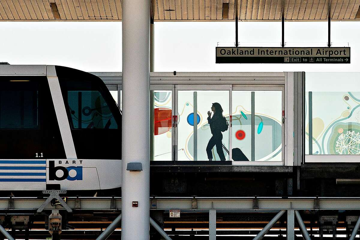 A traveller passes behind security doors as she approaches an Oakland Airport BART connector train on Tuesday, Sept. 24, 2019, in Oakland, Calif.