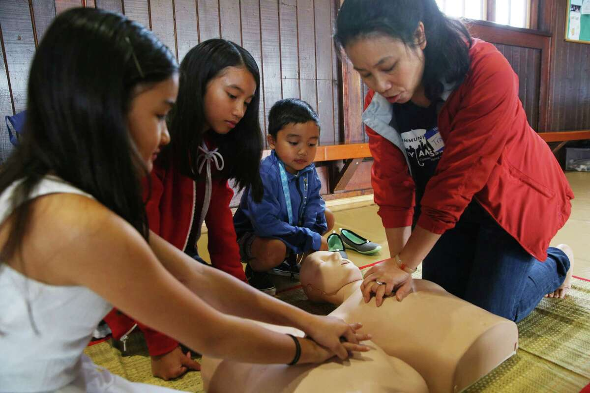 Tram Chung, right, teaches CPR to (from left) Fynix Wolfe, 7, Malina Sorth, 12, and Skylare Cerna, 6, at the Khmer Heath Fair in White Center, Saturday, Sept. 21, 2019. This first ever fair aimed increasing health equity in the Khmer community and providing health screenings, education and prevenative services.