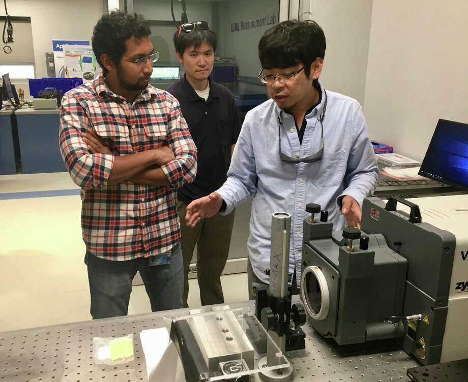 Shaun Chen, right, shows an interferometer machine that measures the quality and characteristics of precision optics, as Guru Pandian (left) looks on, at the newly opened testing lab at ASML in Wilton, Conn., on Thursday, Sept. 6, 2018. Photo: Dan Haar / Hearst Connecticut Media / Stamford Advocate