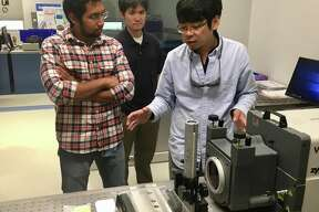 Shaun Chen, right, shows an interferometer machine that measures the quality and characteristics of precision optics, as Guru Pandian (left) looks on, at the newly opened testing lab at ASML in Wilton, Conn., on Thursday, Sept. 6, 2018.